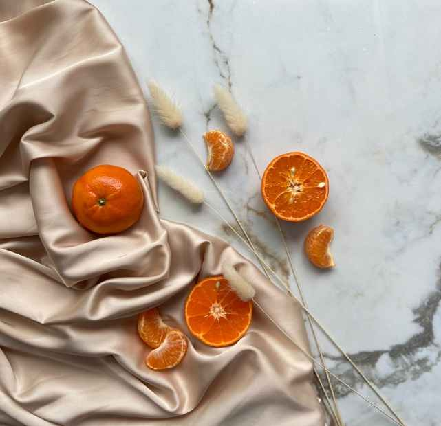 delicious tangerines and oranges on silk fabric