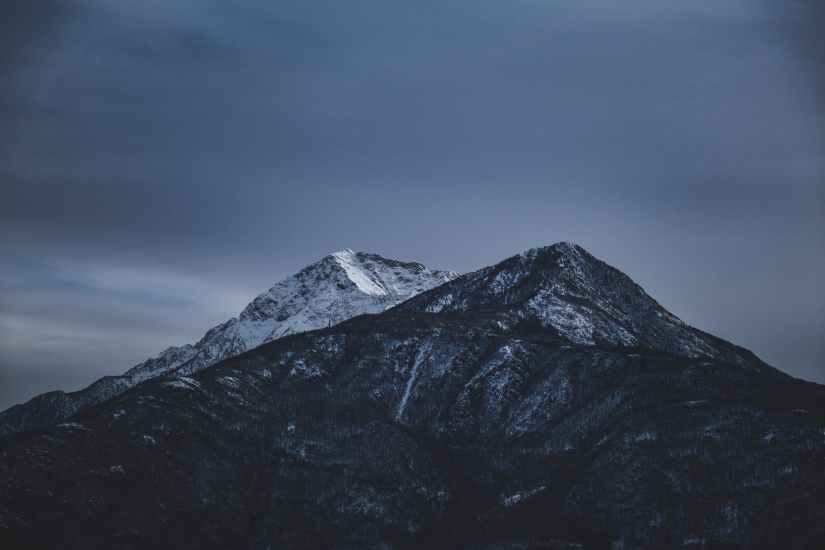 overcast sky over rocky snowy mountains in winter evening