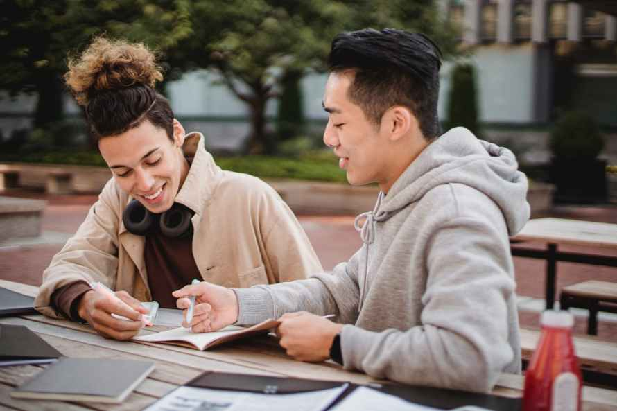 happy diverse male students working on home assignment in park
