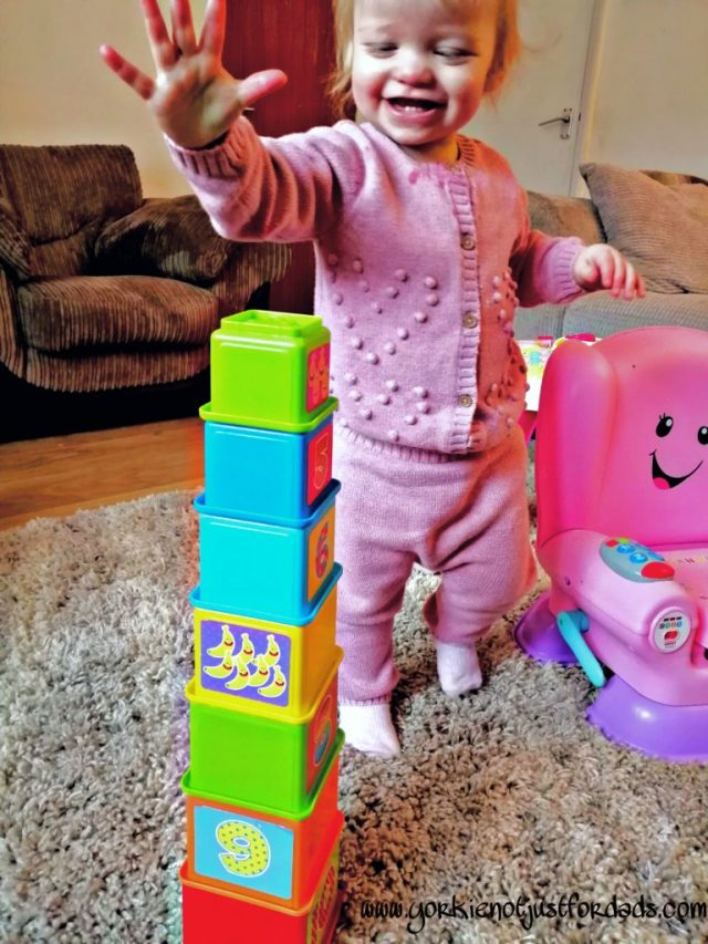 Play time with her Stacking Blocks. Using a learned skill of hand eye Coordination she is able to stack the blocks to create a tower.