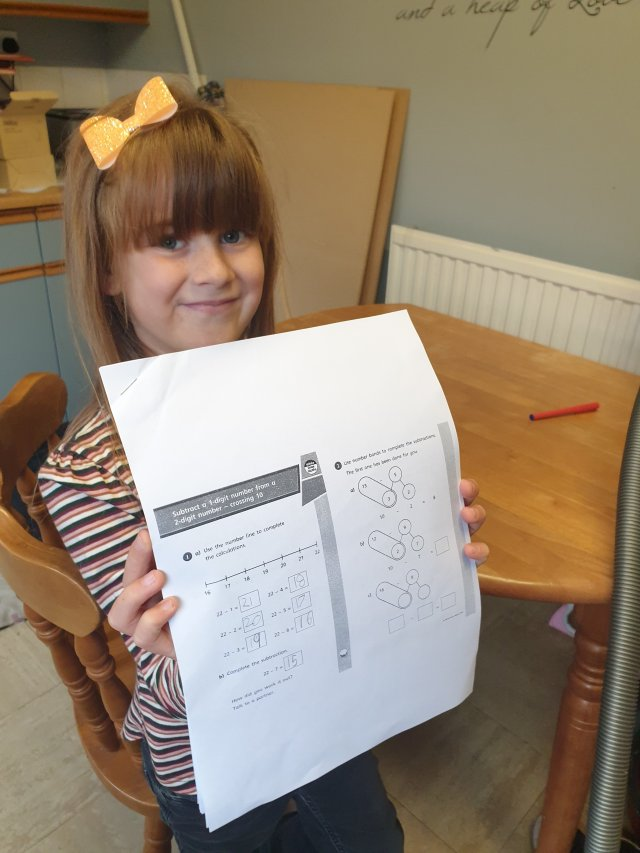 A picture of Titch with her Twinkl Maths workbook provided from school for home schooling while she is in isolation.