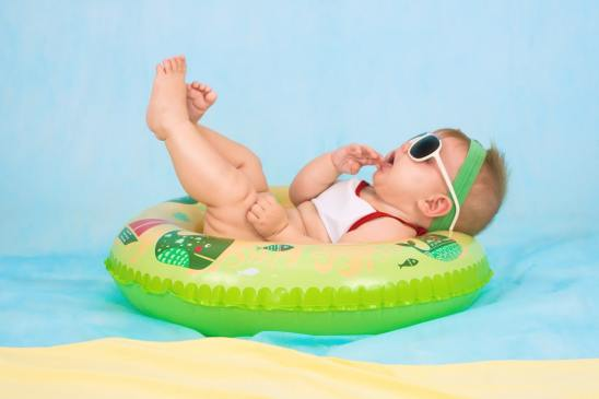 A baby chilling in an inflatable ring in a paddling pool, definitely a great way to keep your baby cool in the heat.