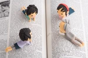 本を眺める人形たち