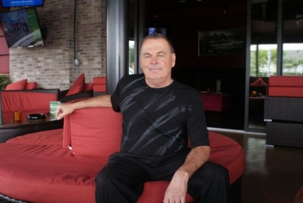 Proprietor Dewey Tomko lounges in the expansive patio of Dewey's Indoor Golf & Sports Grill.