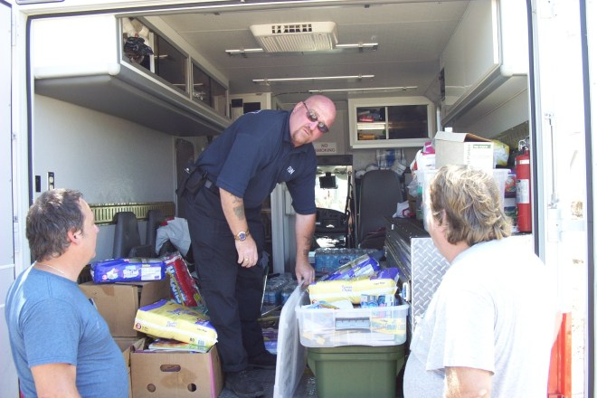 A NYC firefighter hands out out supplies on the Mississippi Gulf Coast in the days following Hurricane Katrina.