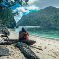 couple sitting on a log on a beach in the Philippines looking out into the water secret beach hidden beach matinloc shrine star beach helicopter island