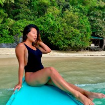 jenny chu in a black bikini sitting in front of a long tail boat in el nido philippines