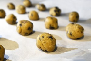 Cookies on top of wax paper going into oven