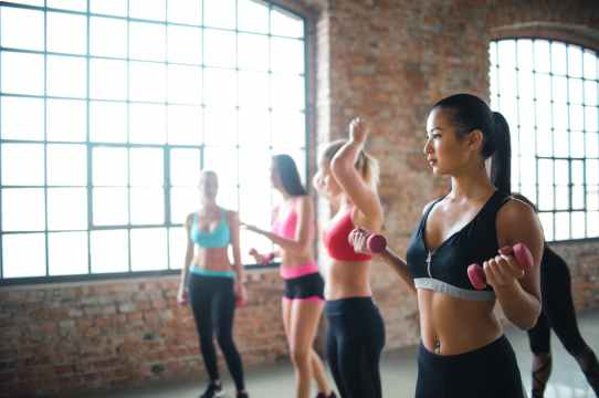 young ethnic fit woman in group training with dumbbells