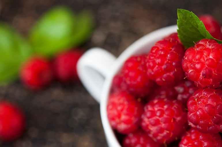 ripe raspberries in white teacup