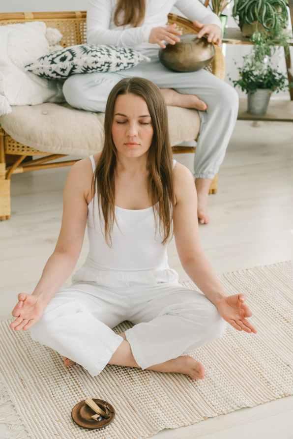 woman meditating with burning sage smudge stick