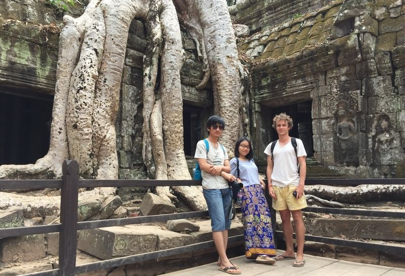 People standing in front of tree at Ta Prohm