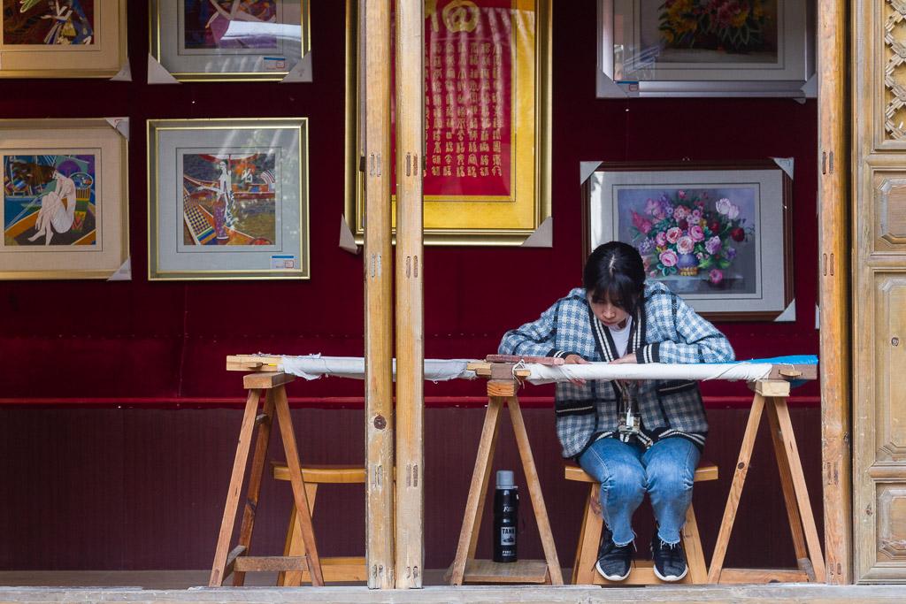 A girl making Naxi embroidery in Baisha