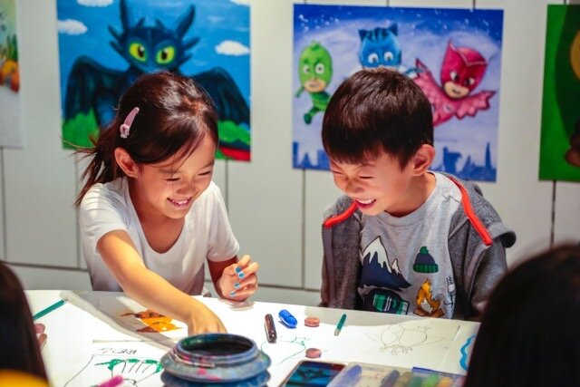 Kids smiling while painting