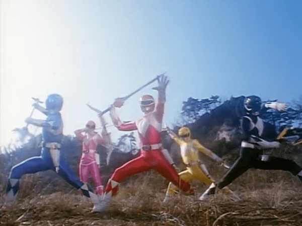 The Power Rangers posing with their weapons.