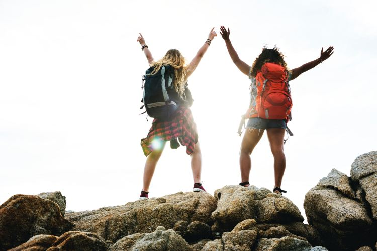 picture of two girls standing on a mountain top