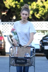 Beverly Hills, CA - Gigi Hadid shops for flowers and beer at Bristol Farms looking casual in multiple necklaces, a torn t-shirt, blue jeans, and pink sneakers. Gigi also takes the time to stop by a nearby magazine rack while sipping on a smoothie with a friend. AKM-GSI October 22, 2016 To License These Photos, Please Contact : Maria Buda (917) 242-1505 mbuda@akmgsi.com sales@akmgsi.com or Mark Satter (317) 691-9592 msatter@akmgsi.com sales@akmgsi.com www.akmgsi.com