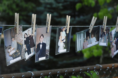 bride and groom timeline of old photos hung on clothespin at backyard wedding