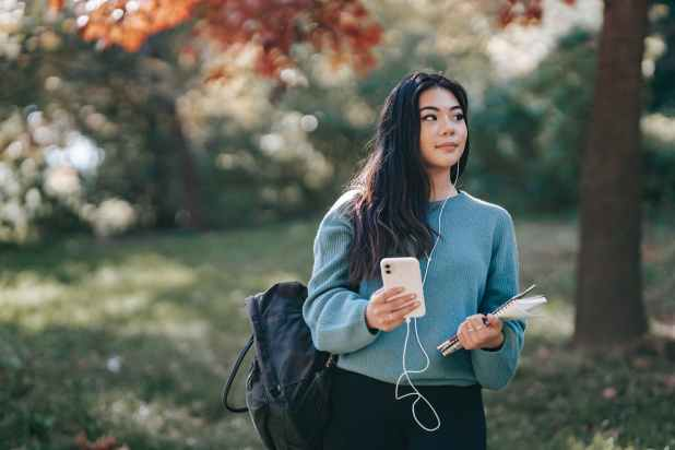 asian woman in earphones with notebook using smartphone in park