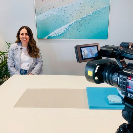 A young woman smiles as she sits at a dining table with a vibrant blue beach painting on the wall behind her whilst a video camera films her in the foreground.
