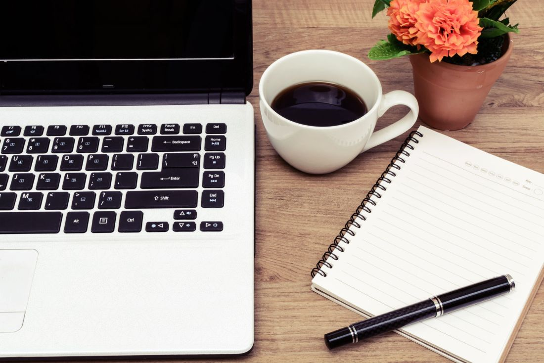 37219545 - laptop and cup of coffee with flower on desk, vintage style