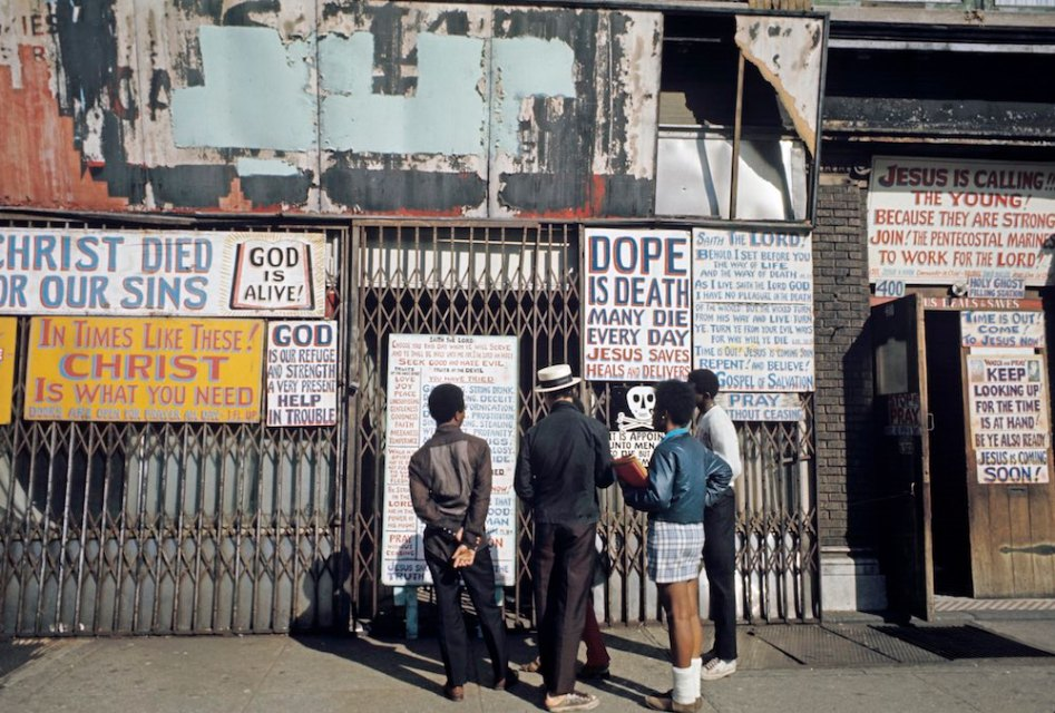 Harlem: The Ghetto. New York City- Harlem- juillet 1970: le ghetto; trois enfants lisent les affiches de propagande pentecÙtiste placardÈes sur un rez-de-chaussÈe d'immeuble et prÙnant l'arrÍt de la drogue. (Photo by Jack Garofalo/Paris Match via Getty Images)