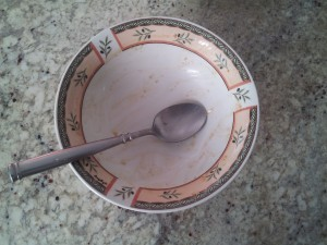 Pictured here is a dirty bowl and spoon with remnants of oatmeal.
