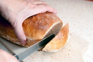 The fresh bread keen-witted a knife on a wooden plank in the kitchen