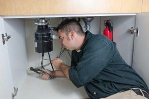 A plumber laying under a house hold sink working on a garbage disposal.