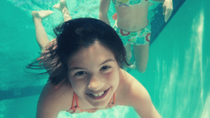 young girl swimming under water