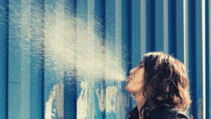 man spitting against a wall