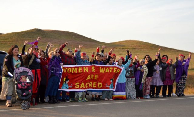 "September 22, 2015-Women from tribal coalitions stand united on the front line at the entrance of the Sacred Stone Camp to tell the world ""Water & Women Are Sacred."" The coalitions came together across Turtle Island-from the northern region of Alaska, across the United States from California to Maine, and along the southern border of New Mexico and Oklahoma to support the Standing Rock Sioux Tribe. The tribal women's coalitions organized to increase safety for native women have member programs representing more than half of all federally recognized Indian Nations. (Photographer: Jacqueline ""Jax"" Agtuca)"