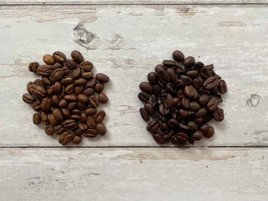 Medium roasted and dark roasted coffee beans next to each other.