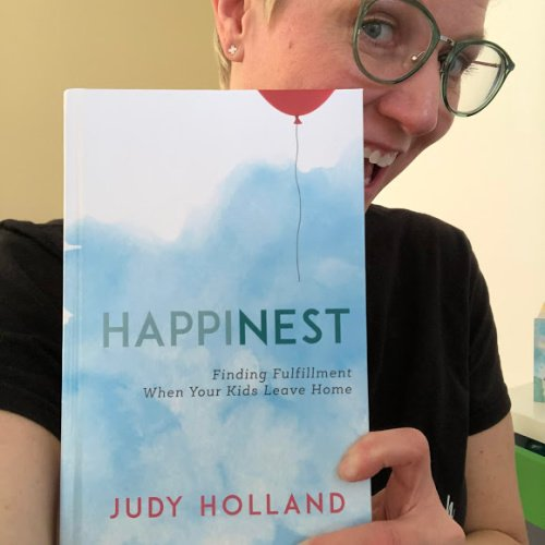 Your Empty Nest Coach, Christine, holds Judy Holland's book: Happinest, Finding Fulfillment When Your Kids Leave Home