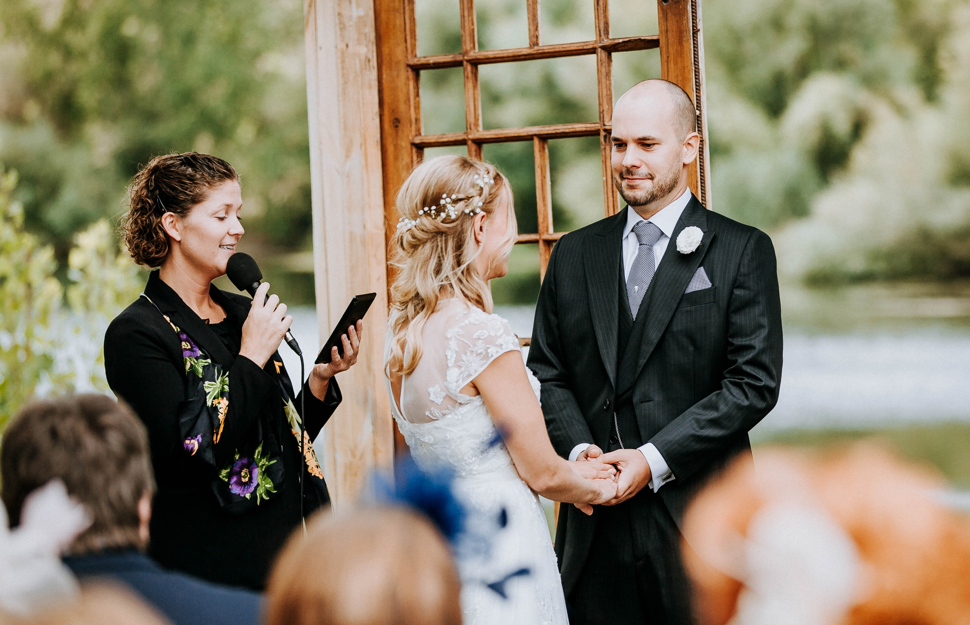 Couple stands in front of the Torres Vedras wedding officiant, bride in a white dress with her back to the camera and the groom, with his face to the camera, smiling at his bride. In the background is a lake.