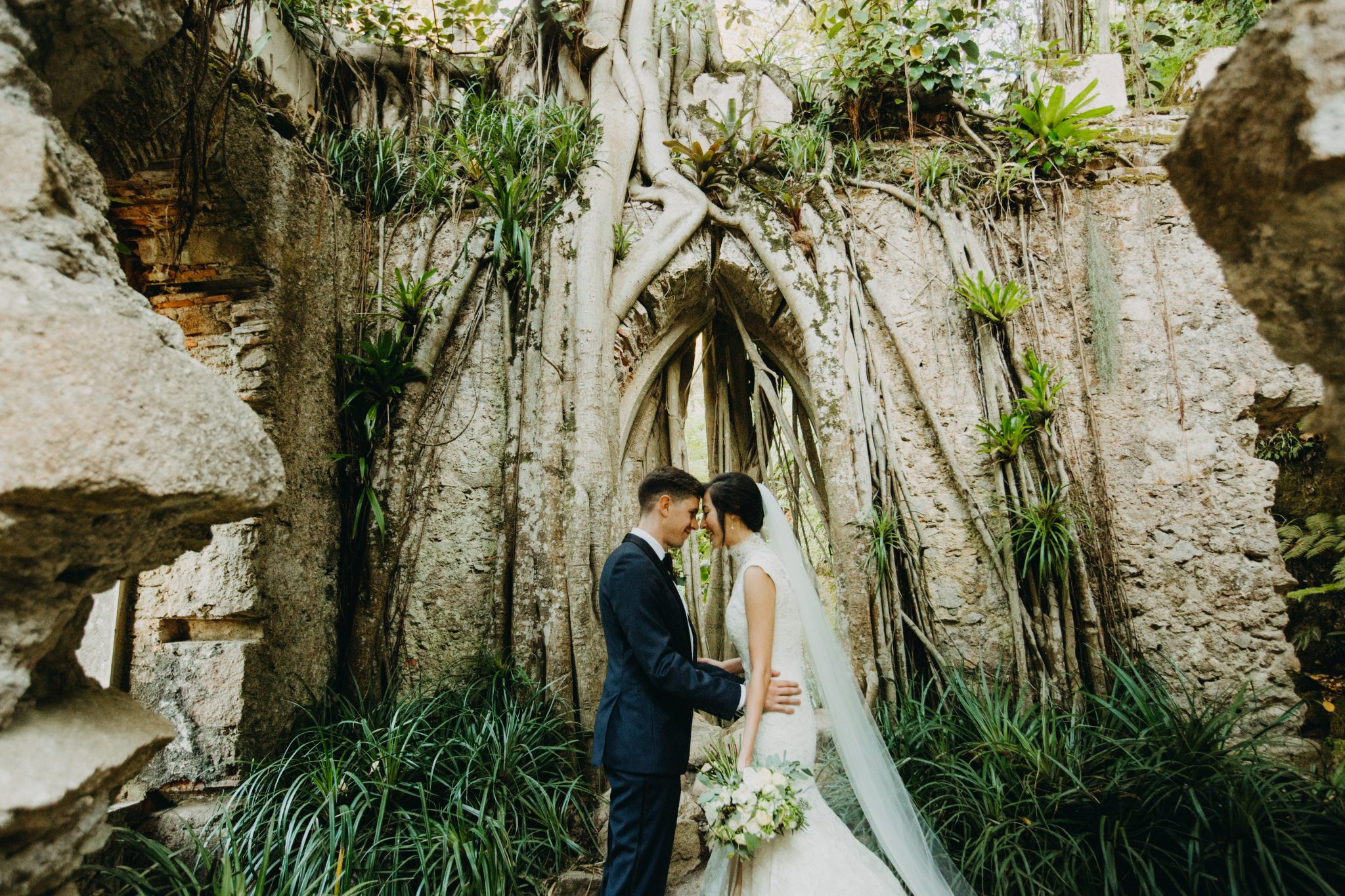 Bride and groom look at each other with their foreheads touching with the ruins of an old church and an overgrown tree in the background.