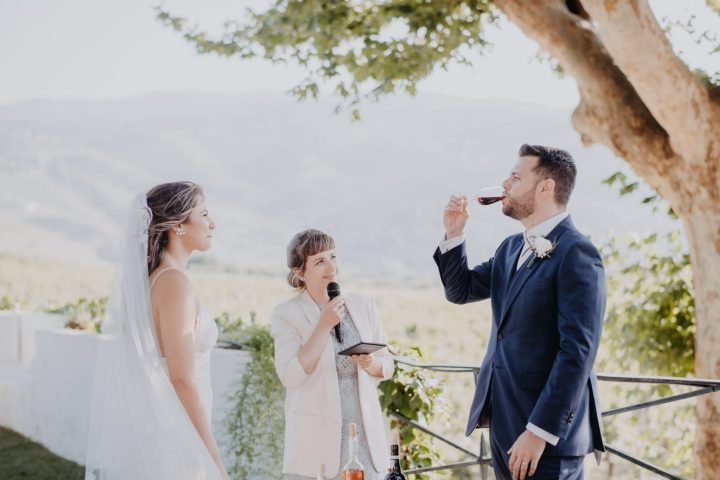 Bride and groom standing before their Douro valley wedding officiant as they participate in the tasting of Port wine with a background of vineyards.