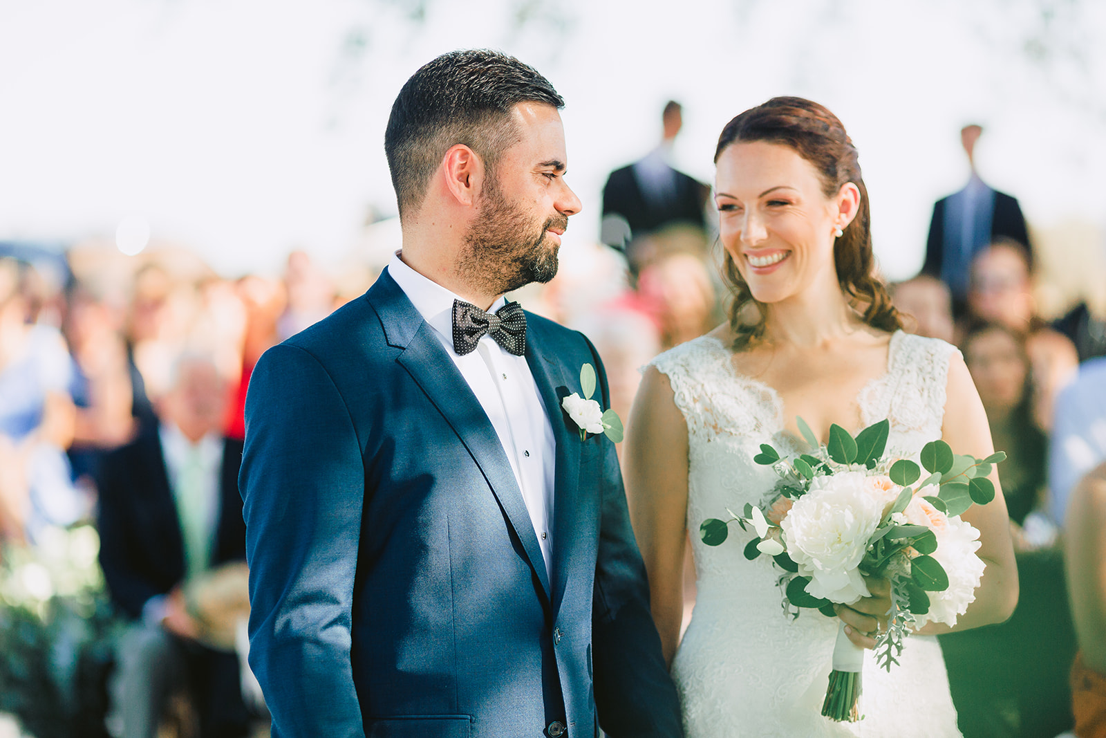 Bride and groom smiling at each other during the symbolic wedding ceremony of their Alentejo wedding officant with guests in the blurred background.