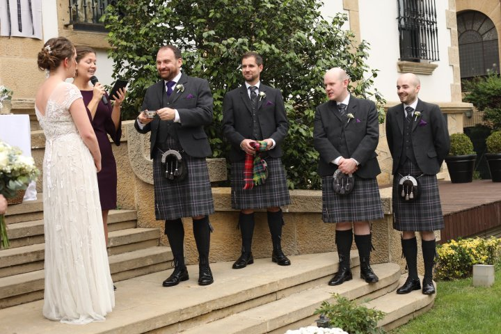 The northern Spain wedding officiant conducting a ritual involving a traditional Scottish love cup that is shared between the couple, the bride is dressed in a long white, lacy gown and the groom and his groomsmen are dressed in kilts.