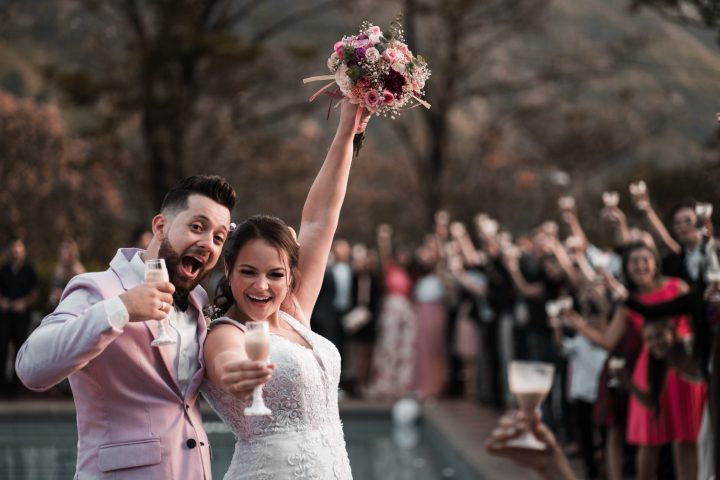 Couple holding glasses and cheering after their Northern Spain wedding officiant led ceremony with guests in the blurry background. Photo credit to Cleyder Duque.