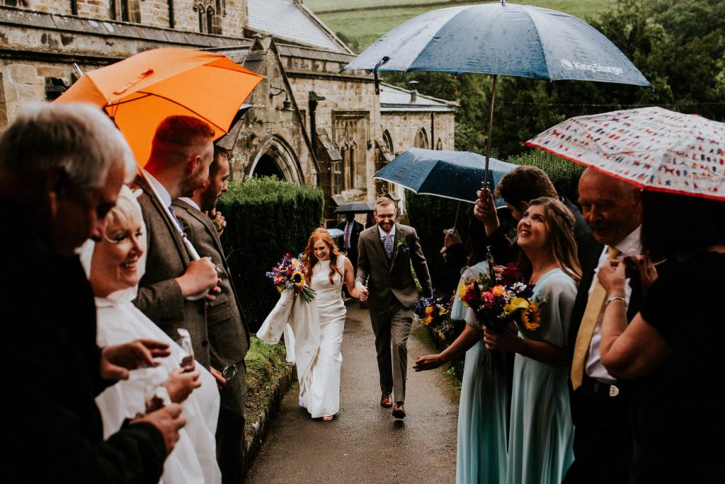 Wedding Guests Lining The Church Path with Umbrellas