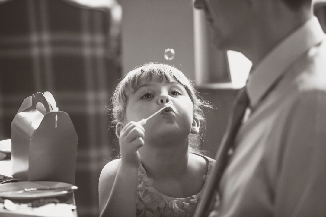 Looking after your wedding guests - Child blowing bubbles at a wedding