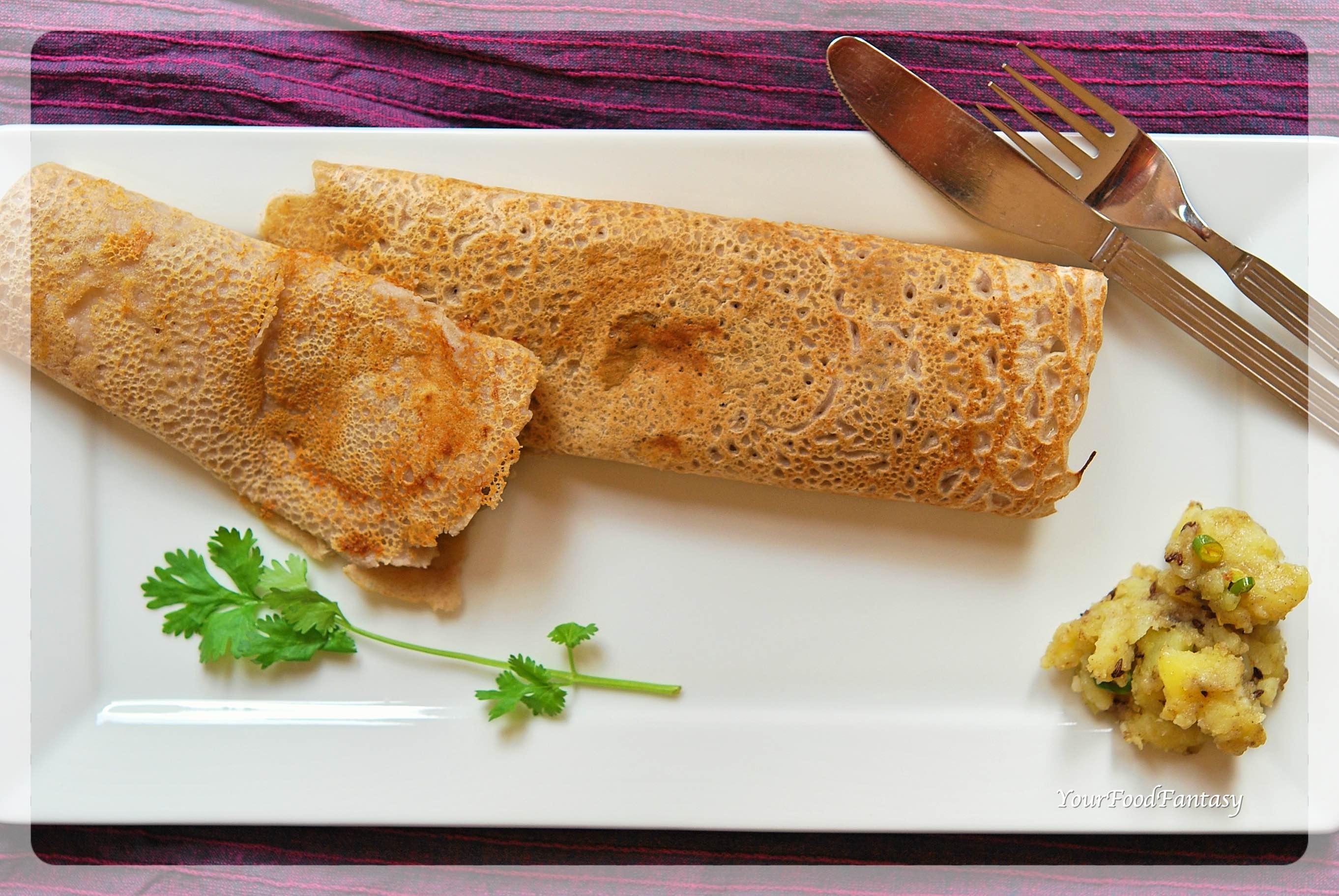 Two kuttu dosa with potato sabzi on a plate