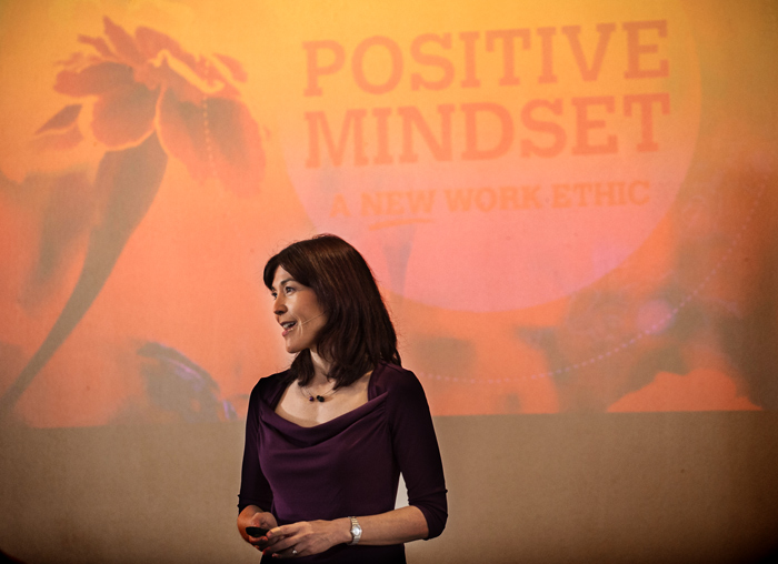 """Alice Inoue standing in front of a projected screen with """"Positive Mindset"""" written on it"""