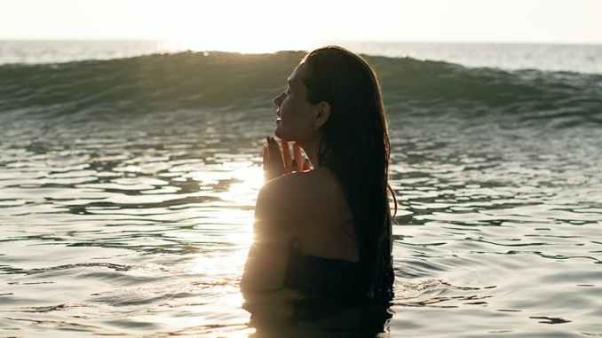 graceful young woman swimming in rippling sea at sundown