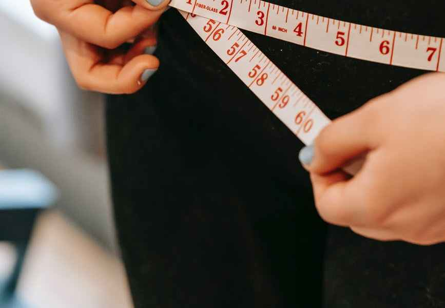 plus size woman measuring hips in gym