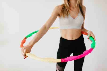 crop slim sportswoman with colorful hula hoop