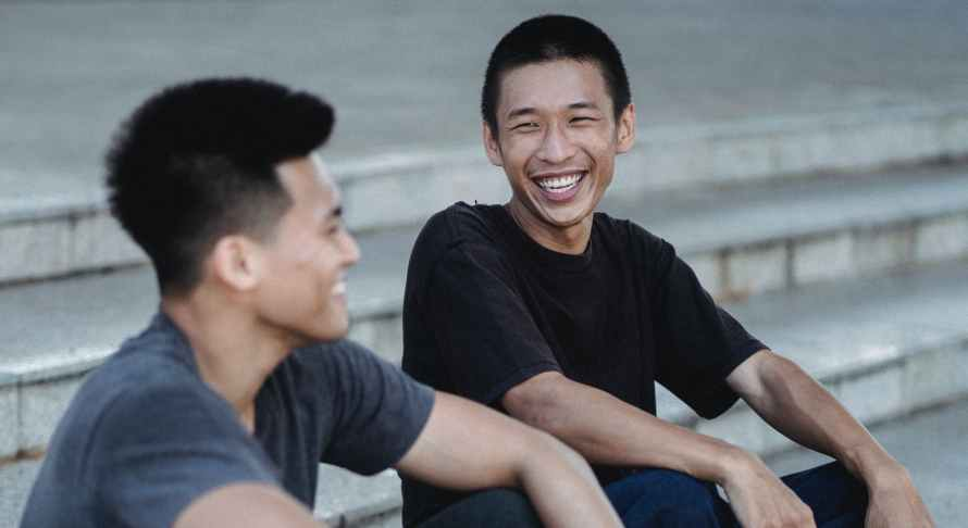 happy asian men sitting on stair and chatting