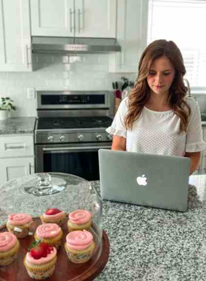 Alana in her kitchen with her laptop and cupcakes