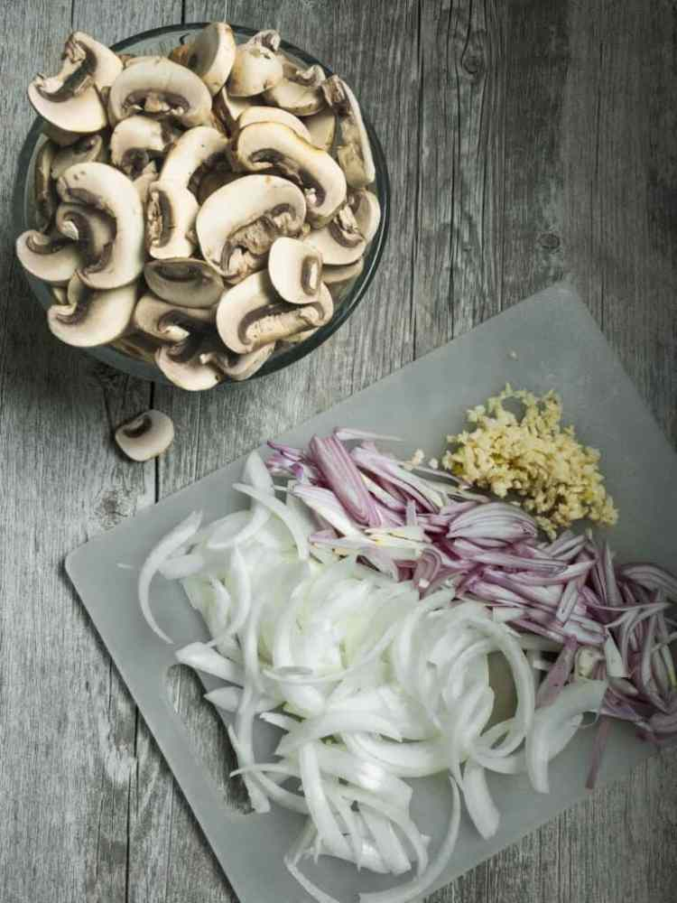chopped mushrooms and onions on a cutting board